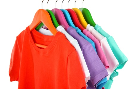 Different shirts on colorful hangers on white background photo