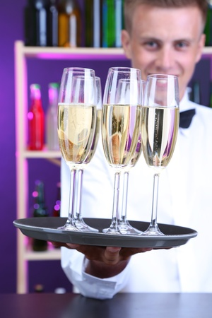 Bartender holding tray with champagne glasses photo