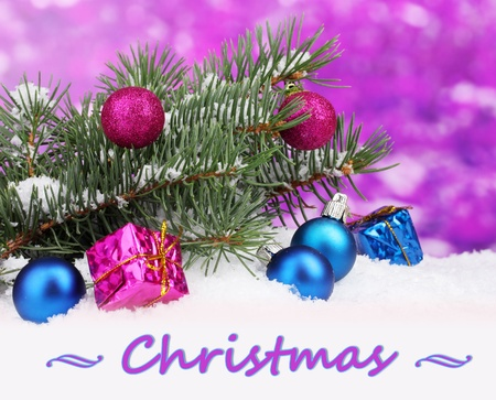 Christmas ball and toy with green tree in the snow on purple background photo