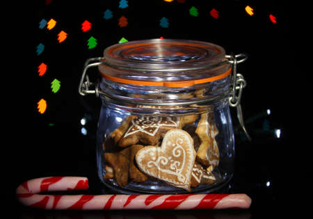 Tasty cookies  in glass bottle on blur lights background photo