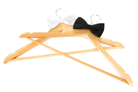 Black and white  bow ties on wooden hangers, isolated on white photo