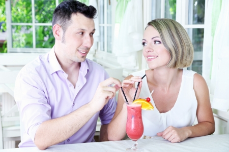Beautiful couple  drinking together cocktail at restaurant Stock Photo - 24367347