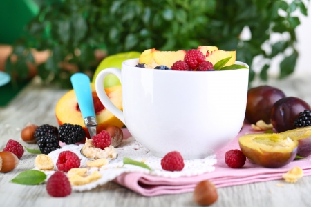 Oatmeal in cup with berries on napkins on wooden table on plant background photo