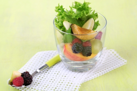 Fruit salad in glass, on wooden background photo