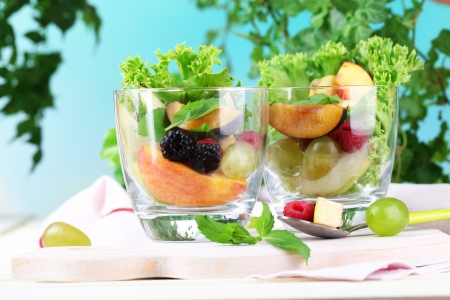 Fruit salad in glasses, on wooden table, on bright background photo