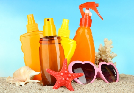 uva: Bottles with suntan cream and sunglasses, on blue background