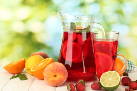sangria in jar and glass with fruits, on wooden table, on green background photo