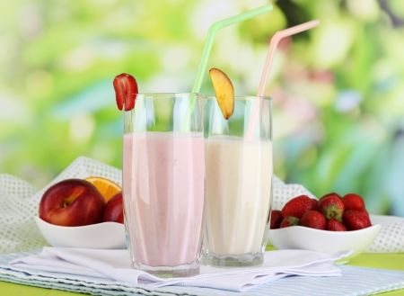 Delicious milk shakes with strawberries and peach on wooden table on natural background photo