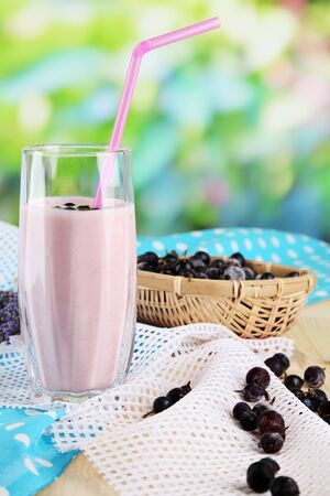 Delicious milk shake with blackberry on wooden table on natural background photo