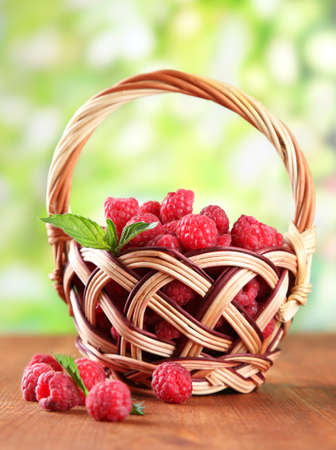 Ripe sweet raspberries in basket on wooden table, on green background photo
