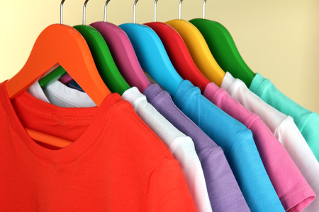 clothing rack: Different shirts on colorful hangers on beige background Stock Photo