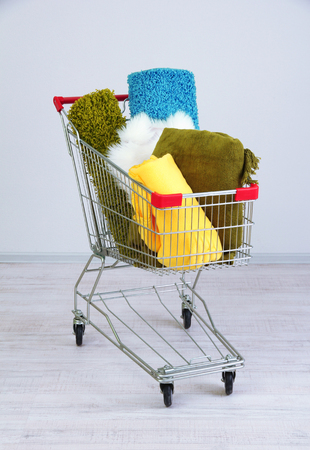 Shopping cart   with colorful carpets and plaids, on color wall background photo