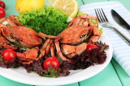 Boiled crabs on white plate with salad leaves and tomatoes,on wooden table background photo