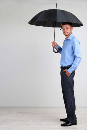 Businessman with umbrella. on gray background photo