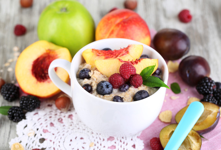 Oatmeal in cup with berries on napkins on wooden table photo