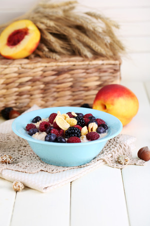 Oatmeal in plate with berries on napkins on wooden table on bright background photo
