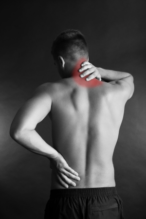 Young man with back pain on grey background photo
