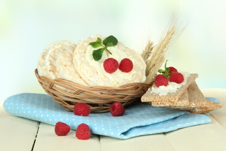 Tasty crispbread with berries in wicker basket, on white table photo