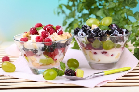 Fruit salad in glass bowls, on wooden table, on bright background photo