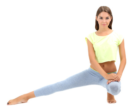 Young beautiful fitness girl doing yoga exercise isolated on white photo