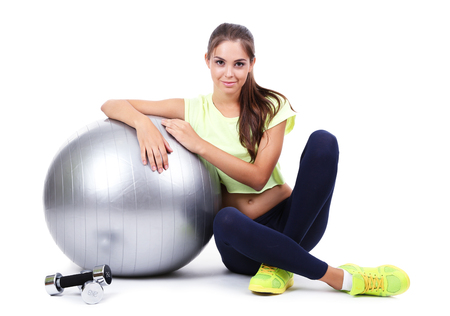 Young beautiful fitness girl with grey ball isolated on white photo