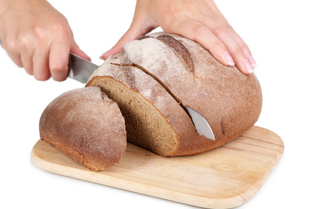 Cutting bread on wooden board isolated on white photo