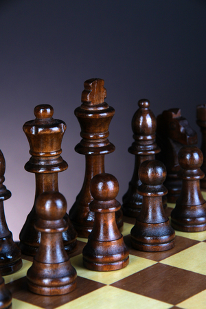 Chess board with chess pieces on dark color background photo