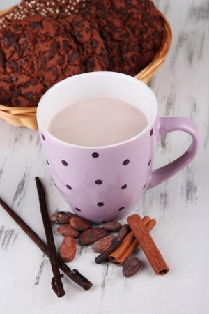 Cocoa drink  with spices and cookies on wooden background photo