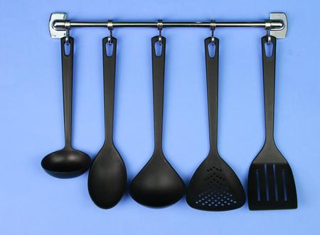 Black kitchen utensils on silver hooks, on blue background photo
