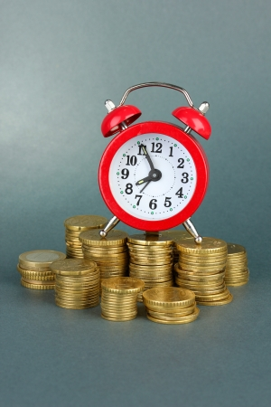 Alarm clock with coins on grey background photo
