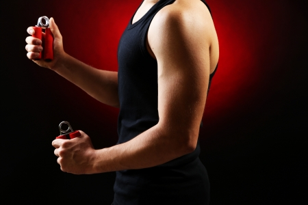 Handsome young muscular sportsman with expanders, on dark background Stock Photo - 22254690