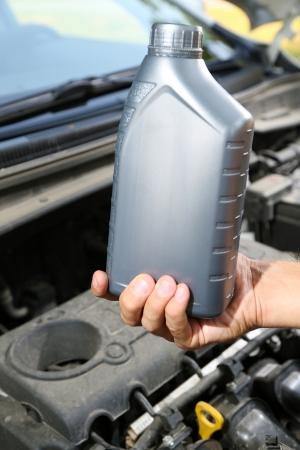 bottleneck: Auto mechanic hand holding motor oil  Stock Photo