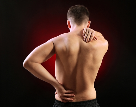 aching muscles: Young man with back pain, on red background