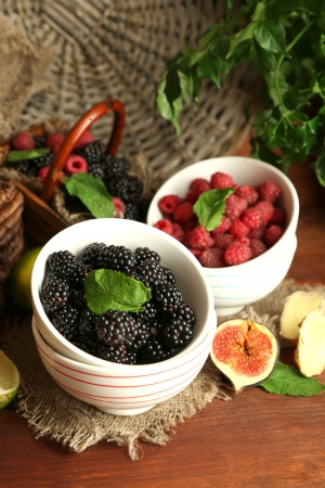 Assortment of juicy fruits and berries on wooden background photo