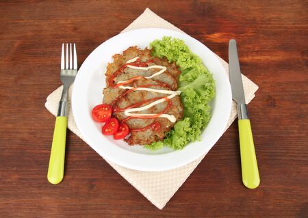 Potato pancakes on plate, on wooden background photo