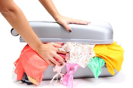 Suitcase with no neatly folded things isolated on white photo