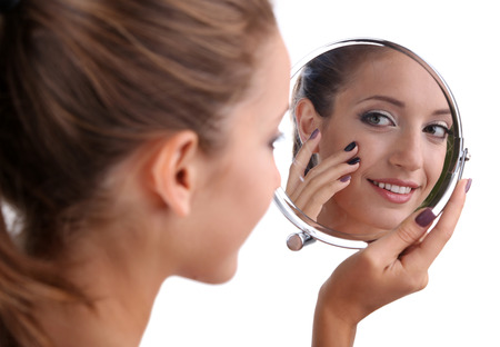 glowing skin: Beautiful girl preens before small mirror isolated on white Stock Photo