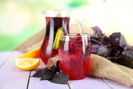 lemon juice: Red basil lemonade in jug and glass, on wooden table, on bright background