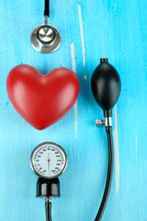 Tonometer, stethoscope and heart on wooden table close-up Stock Photo - 22323213