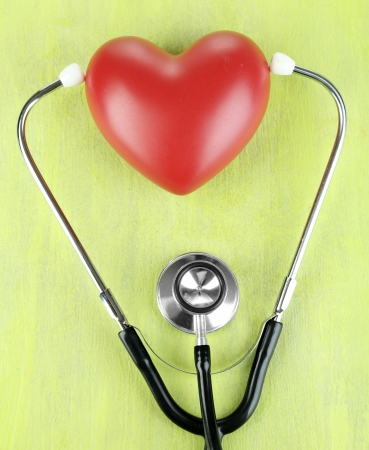 Stethoscope and heart on wooden table close-up photo