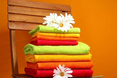 Towels and flowers on wooden chair on orange background