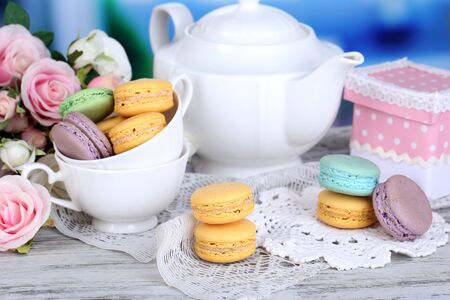 Macaroons in bowl on wooden table on room background photo