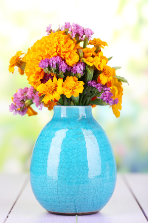 flower vase: Bouquet of marigold flowers in vase on wooden table on natural background