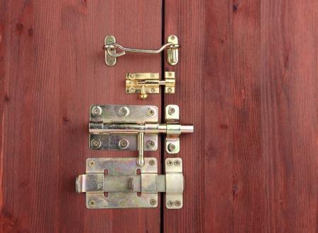 pawl: Perni metallici, serrature e ganci in porta di legno close-up