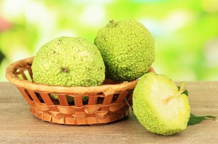 hedgeapple: Osage Orange fruits (Maclura pomifera) in basket, on wooden table, on nature background