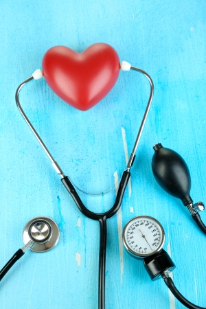 Tonometer, stethoscope and heart on wooden table close-up Stock Photo - 22353376