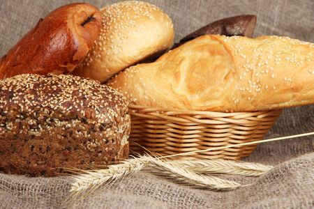 Baked bread in wicker basket on burlap background photo