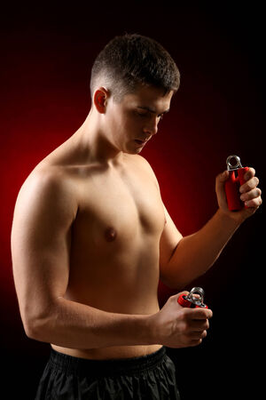 Handsome young muscular sportsman with expanders, on dark background photo