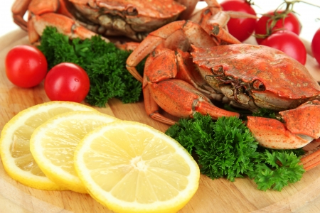 Boiled crabs with lemon slices and tomatoes, on wooden board, close up photo