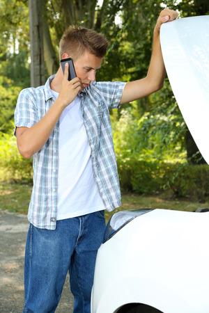 auto insurance: Man calling repair service after car breakdown